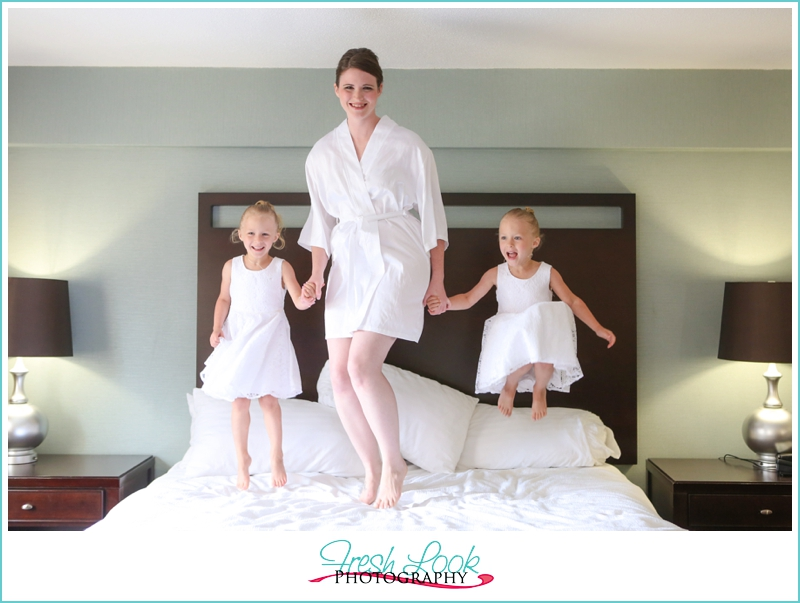 mommy and daughters jumping on bed