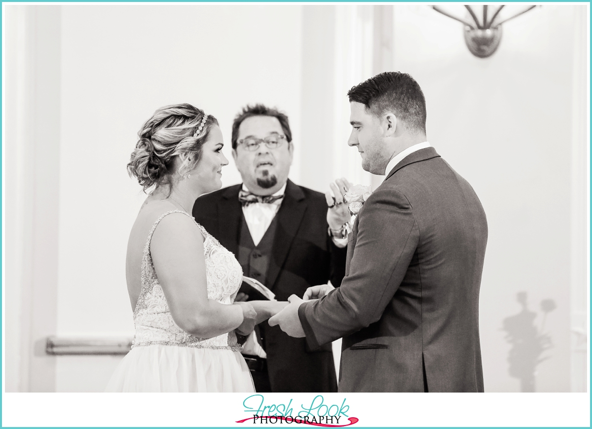 bride and groom exchanging rings during the wedding