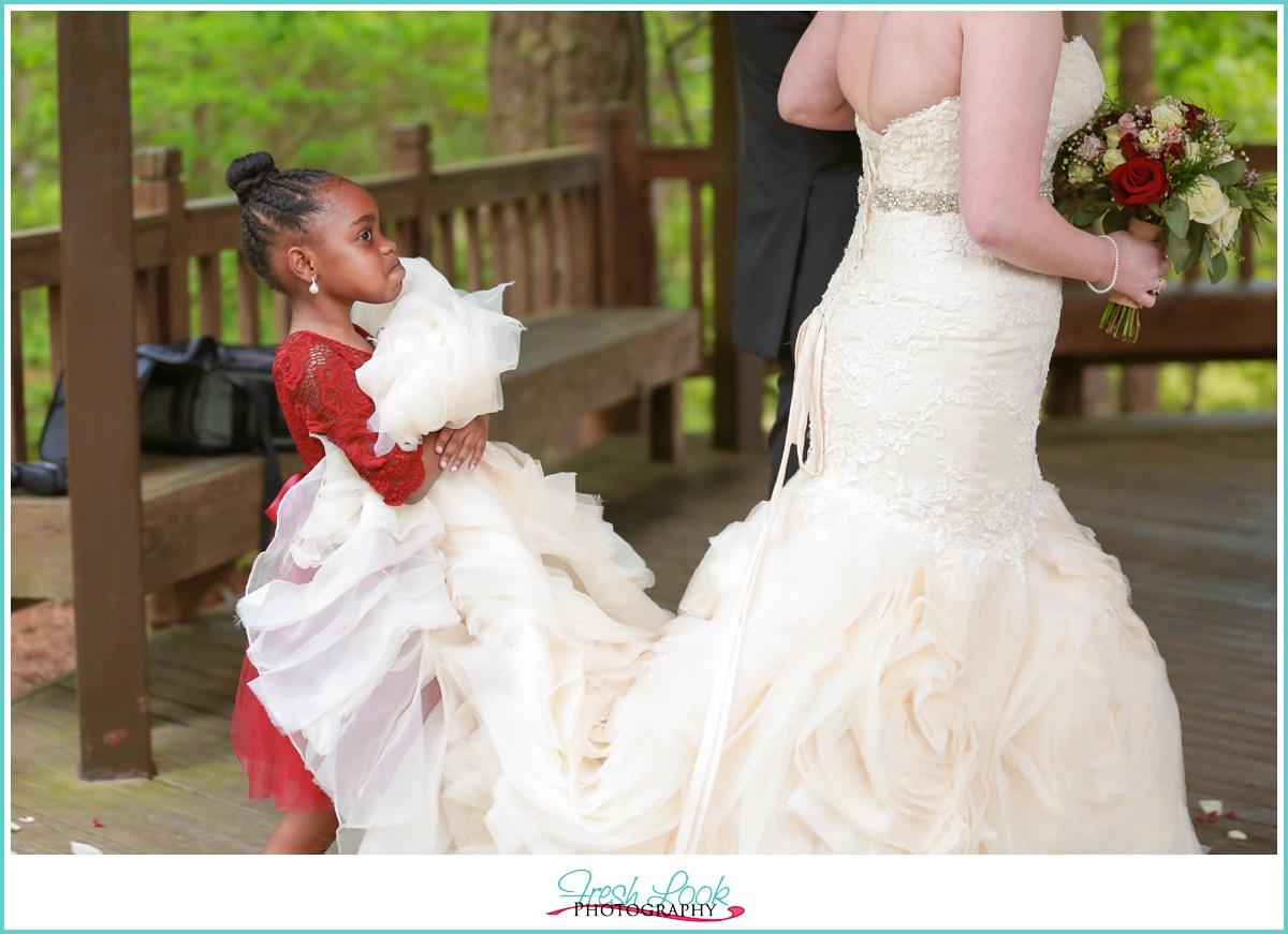 Flower girl holding brides train