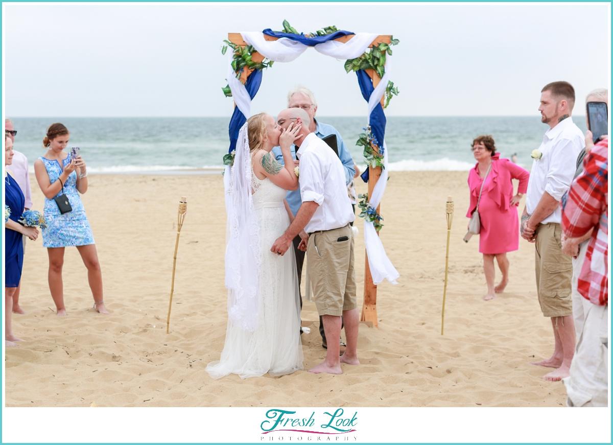 beach ceremony wedding kiss