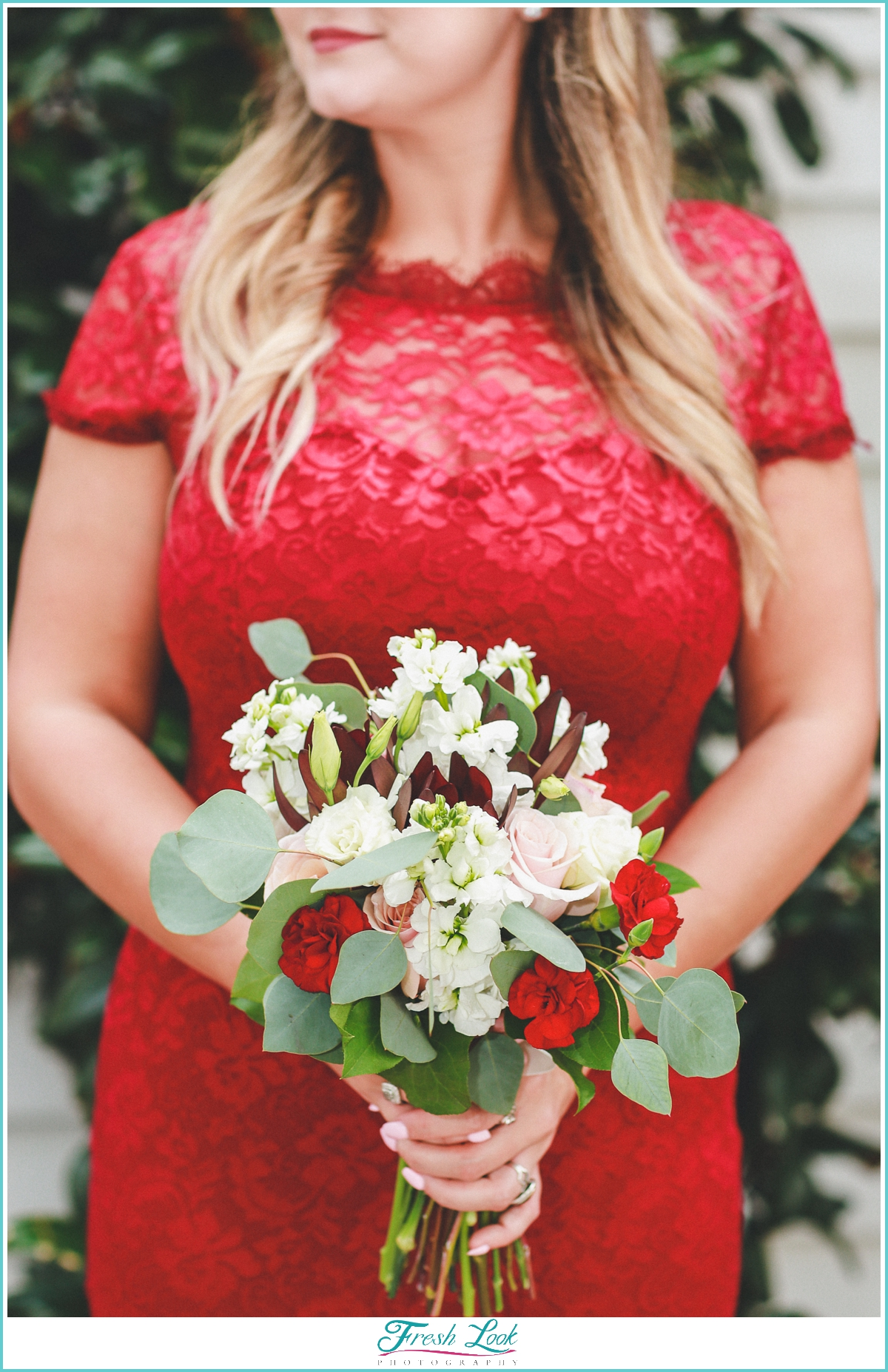 bridesmaid in red holding bouquet