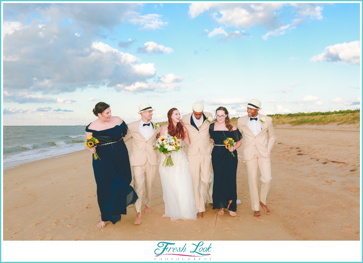 bridesmaids and groomsmen walking on the beach