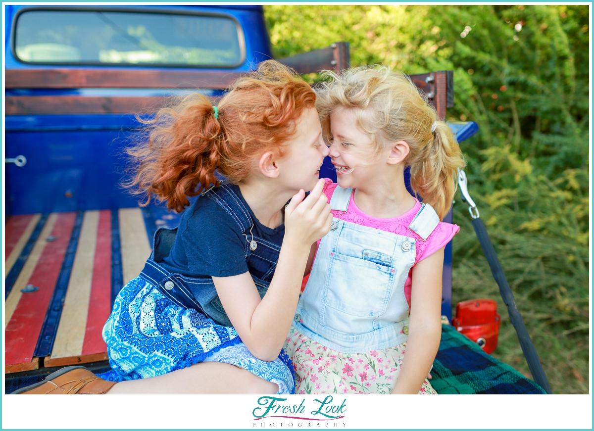 sisters snuggling in vintage truck