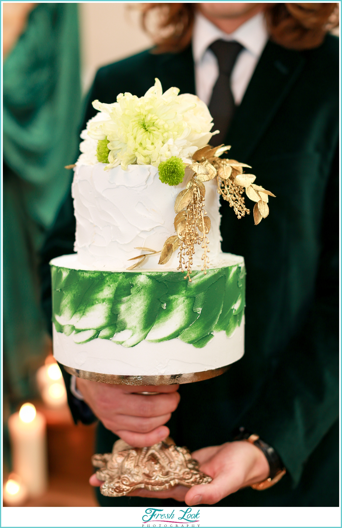 groom holding green and gold cake