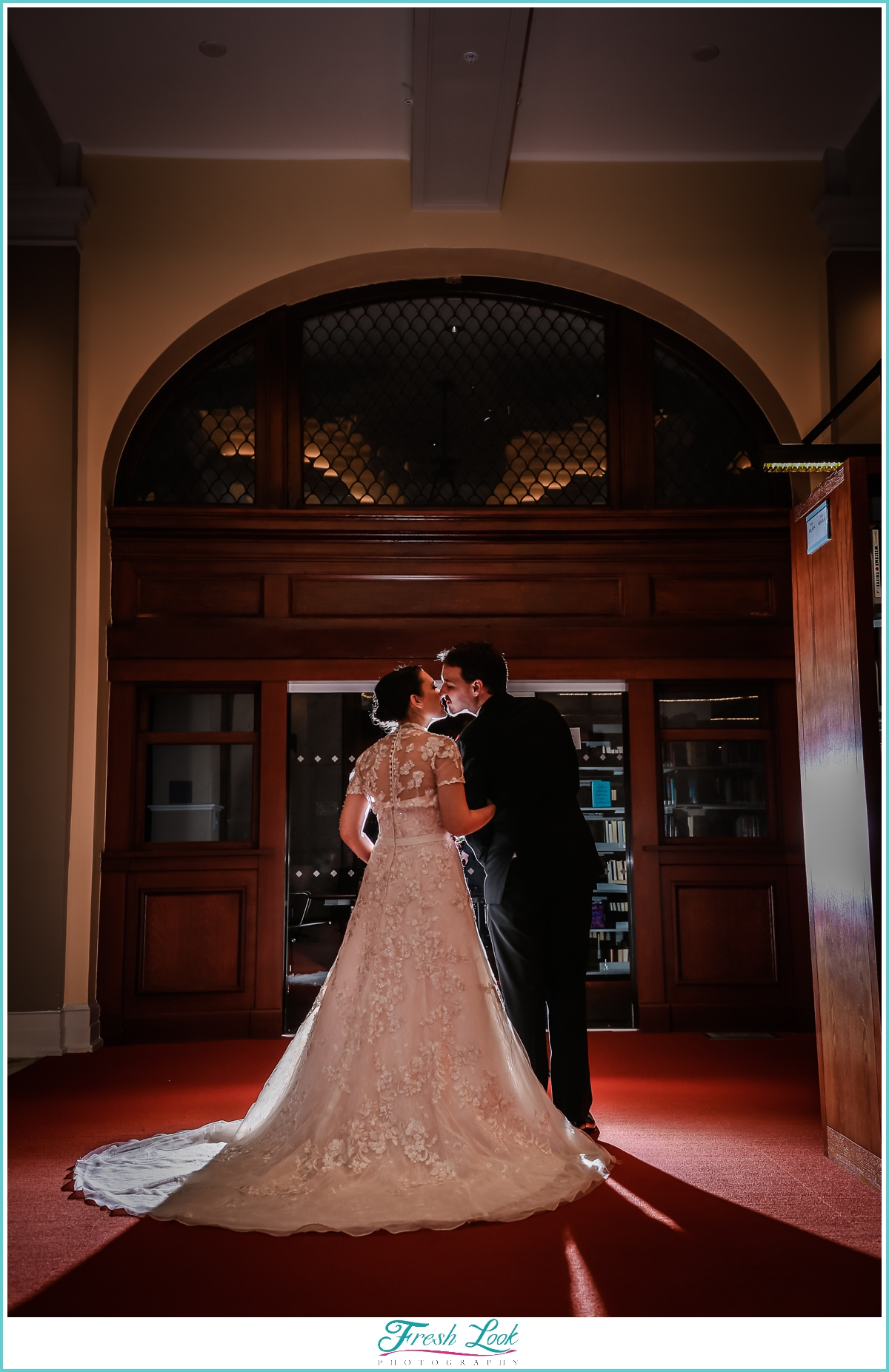 romantic bride and groom kiss in the library