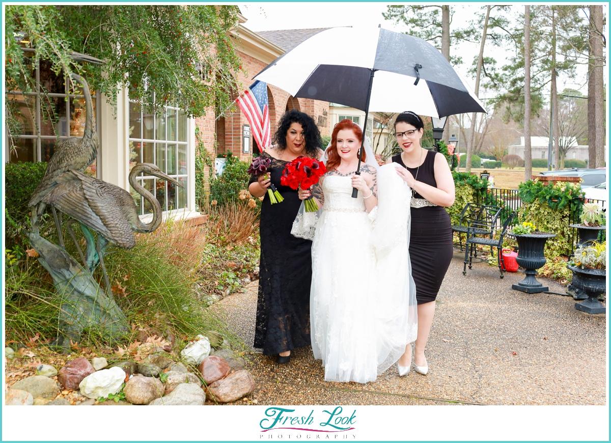 bride and bridesmaids walking through the rain