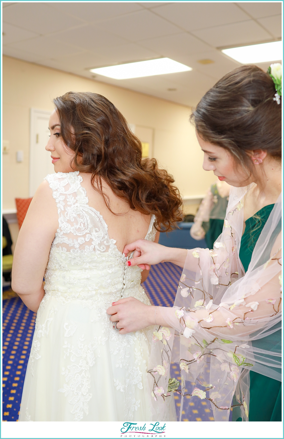 bride being buttoned into her dress