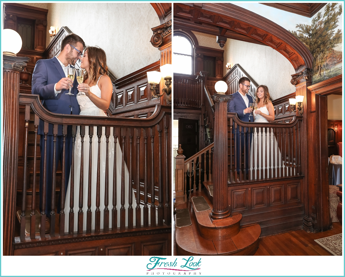 bride and groom toasting on the stairs
