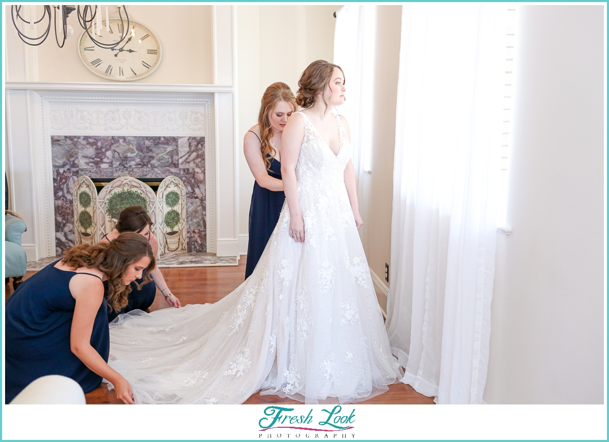 bride getting wedding dress on