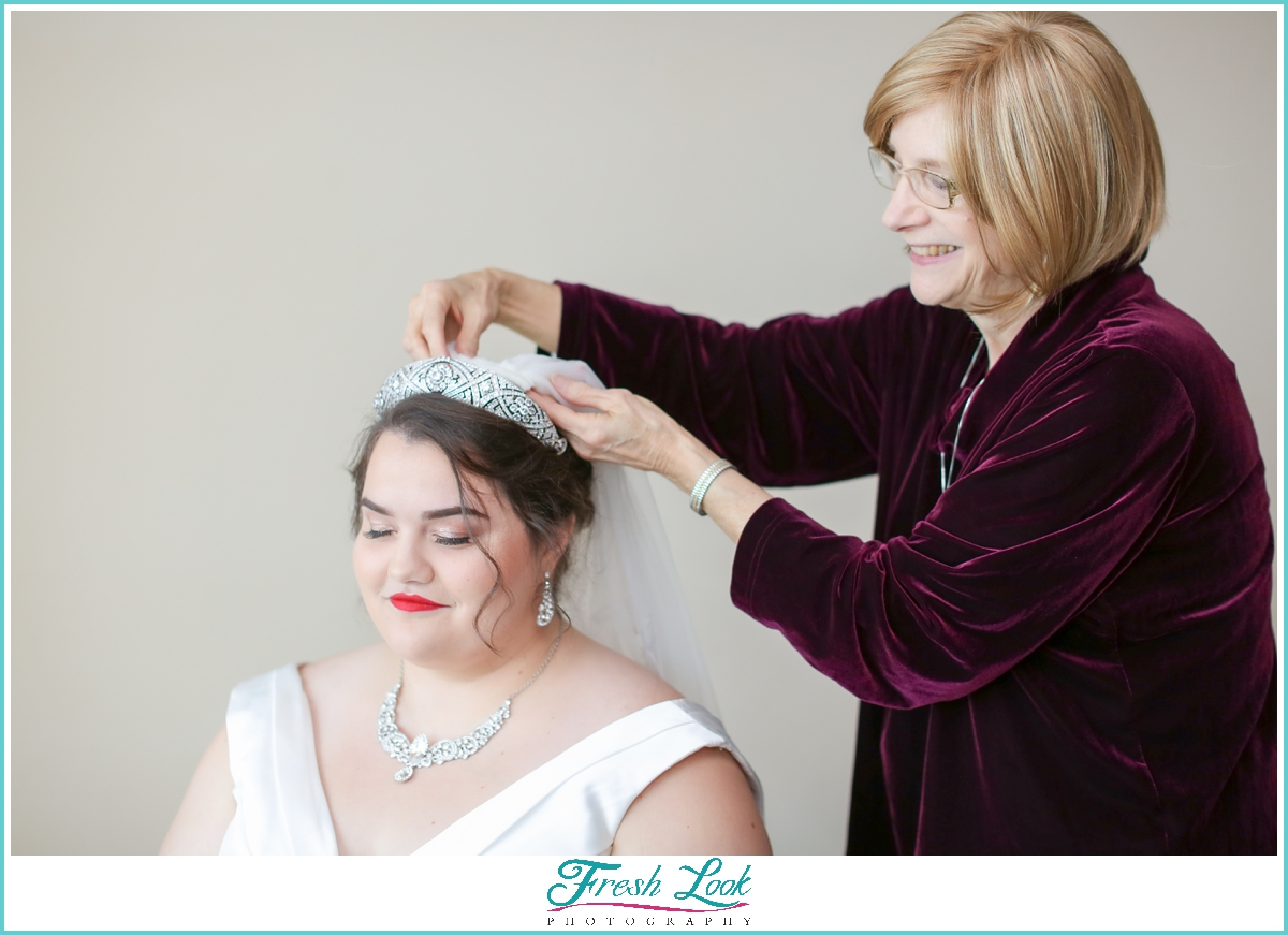 mom putting veil on bride