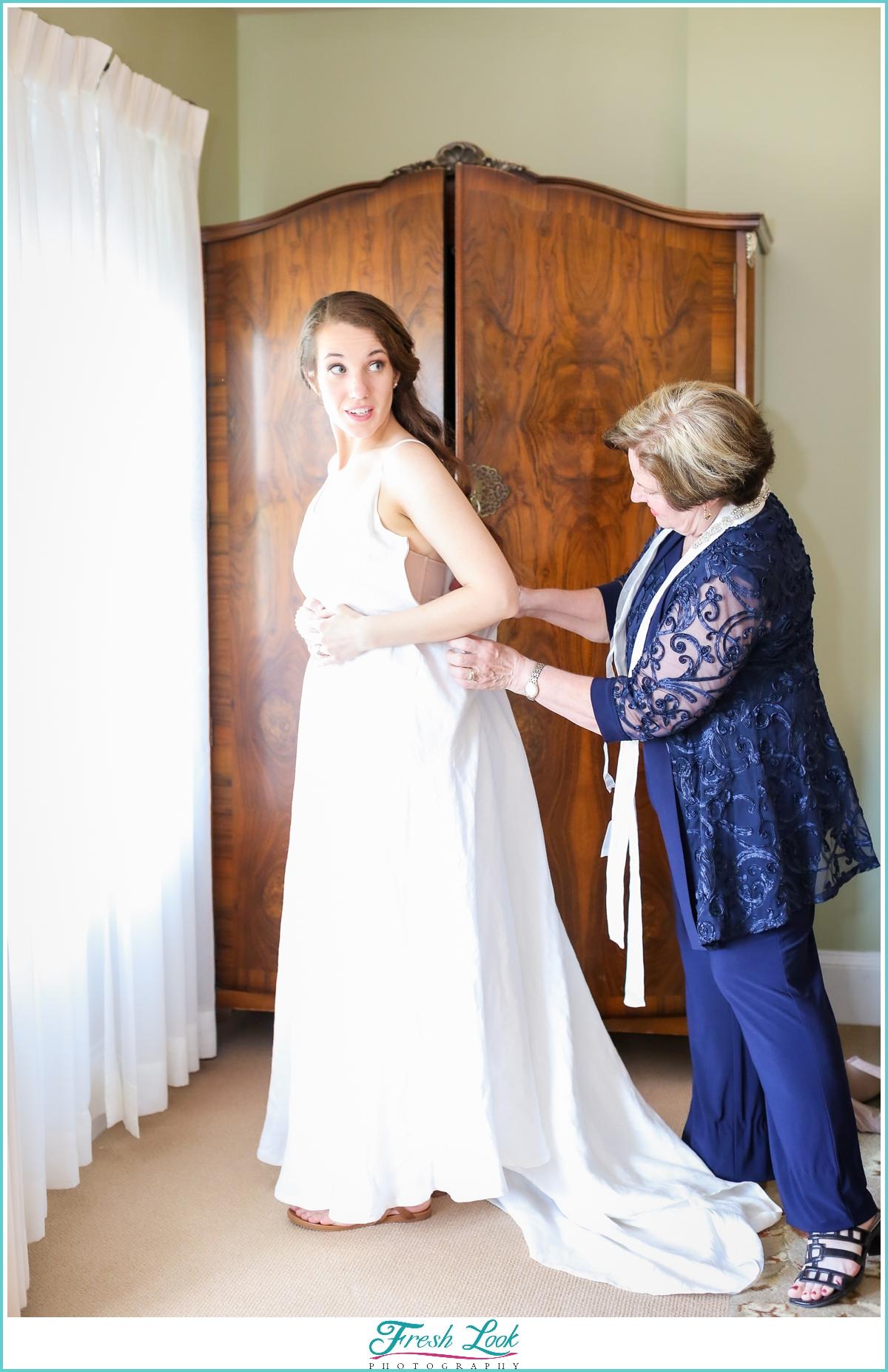 mom helping bride with wedding dress